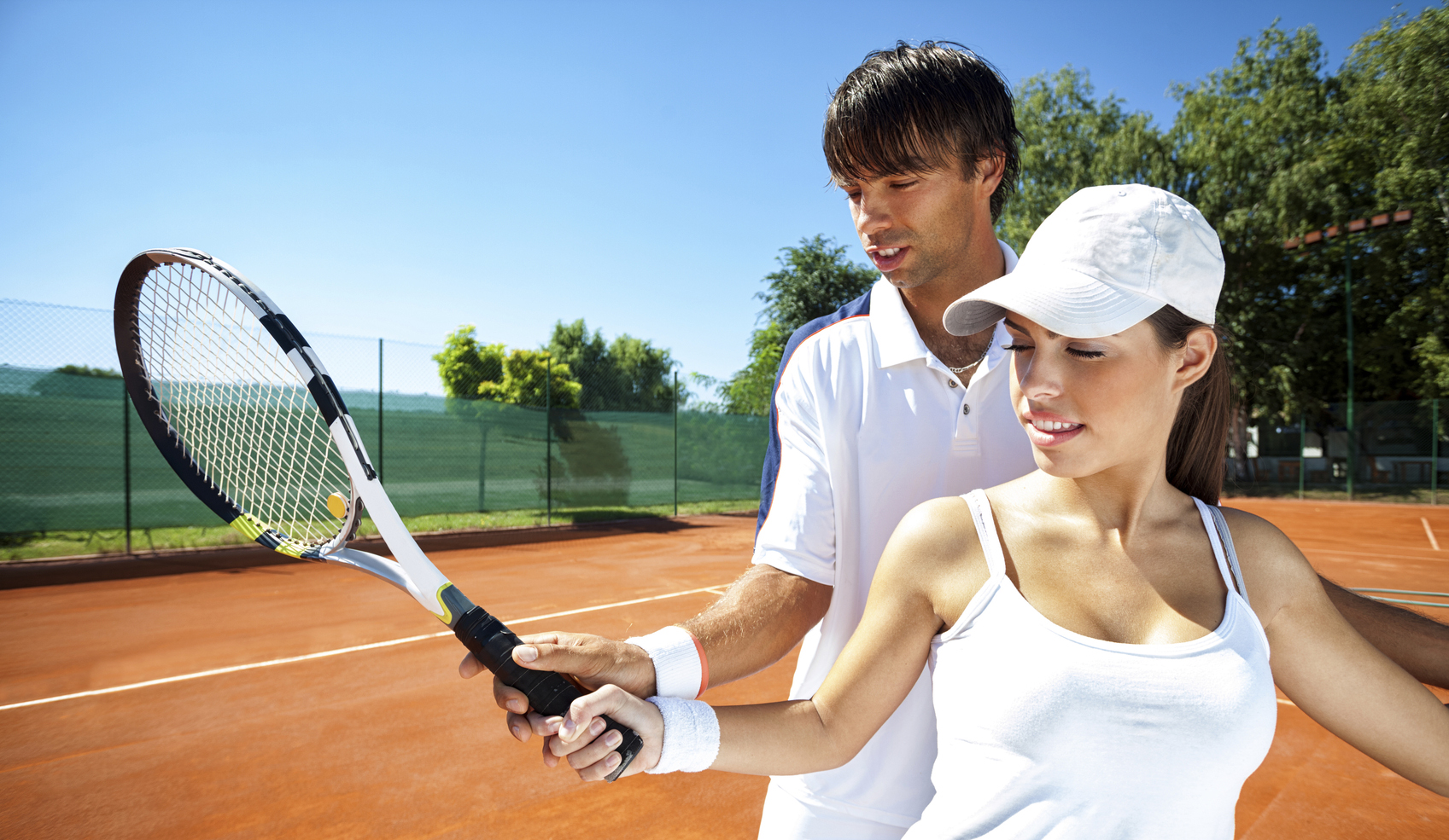 Trainer teaching a female how to play tennis