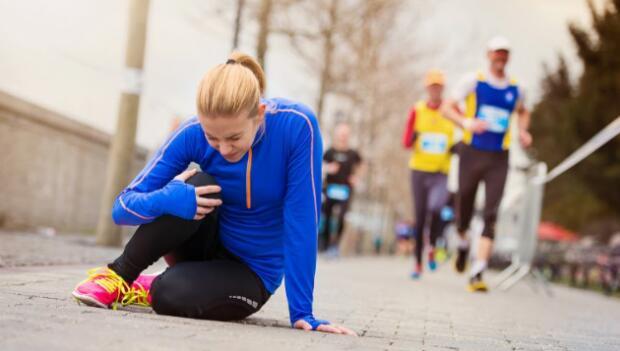 Female Runner Clutching Injured Knee