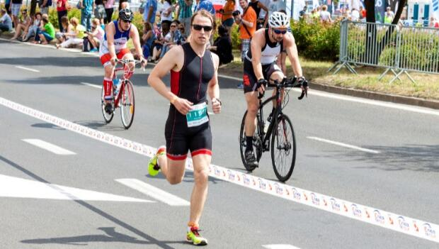 Runner and Cyclists in Triathlon Race