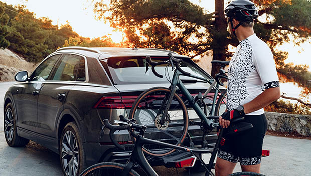 cyclist with a car with a bike rack