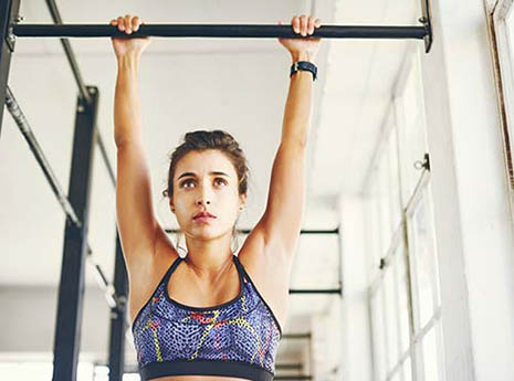Woman+on+a+pull up+bar front