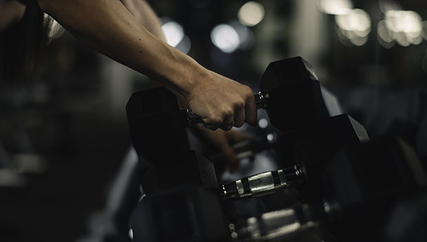 person-picking-up-dumbbells-from-a-rack