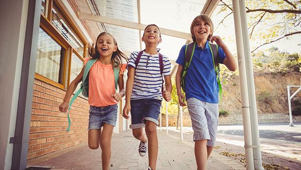 three-kids-running-down-the-hall-at-school