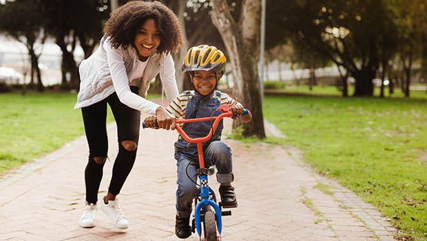 mother teaching son to ride a bike