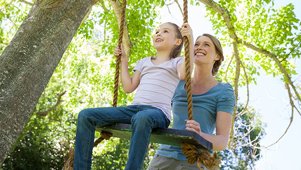 mother pushing daughter on a tree swing