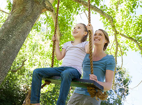 Mother+pushing+daughter+on+a+tree+swing front