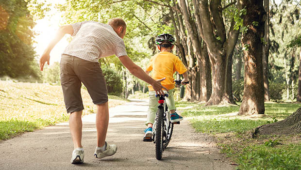 dad with son riding a bike
