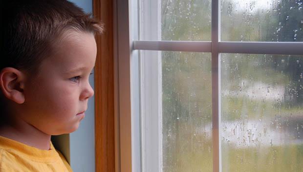kid at a rainy window