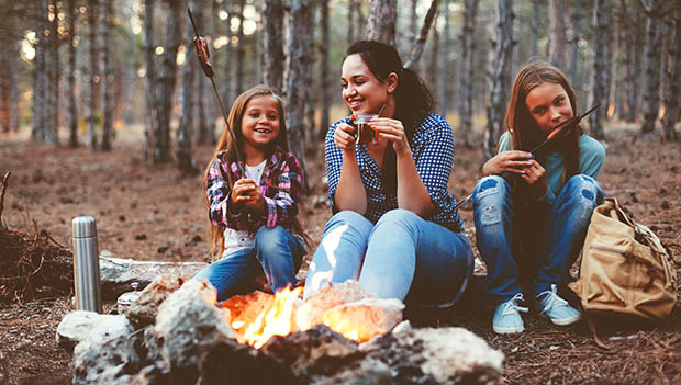 family eating around a campfire