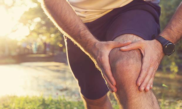 Man grasping knee