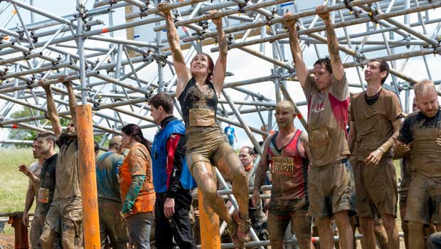 Athletes compete in a mud run